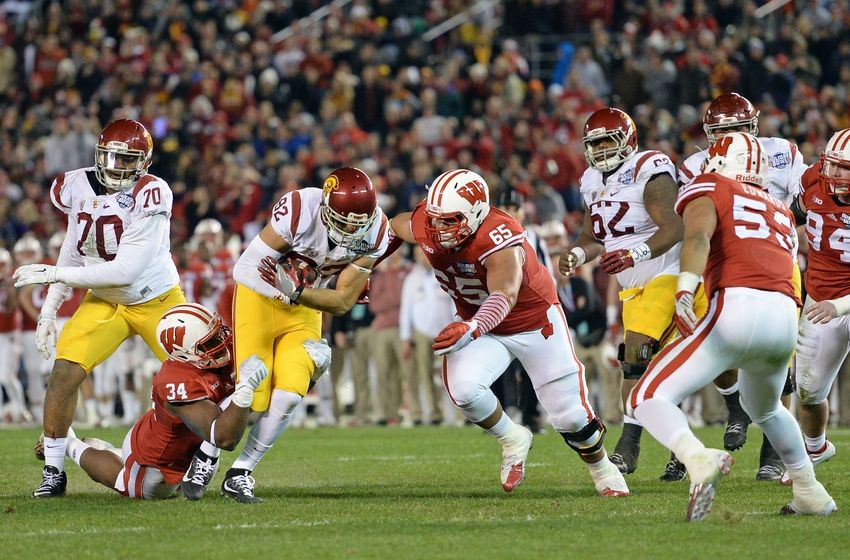 Dec 30, 2015; San Diego, CA, USA; USC Trojans tight end Tyler Petite (82) is defended by Wisconsin Badgers defensive end Chikwe Obasih (34) and defensive lineman Olive Sagapolu (65) during the second quarter in the 2015 Holiday Bowl at Qualcomm Stadium. Mandatory Credit: Jake Roth-USA TODAY Sports