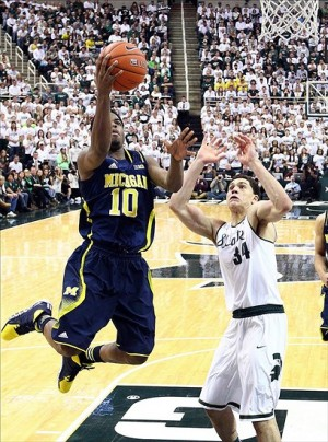 Jan 25, 2014; East Lansing, MI, USA; Michigan Wolverines guard Derrick Walton Jr. (10) drives to the basket against Michigan State Spartans forward Gavin Schilling (34) during the 1st half of a game at Jack Breslin Student Events Center. Mandatory Credit: Mike Carter-USA TODAY Sports