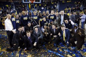 Mar 8, 2014; Ann Arbor, MI, USA; Michigan Wolverines players and coaches pose with the regular season Big Ten championship trophy after the game against the Indiana Hoosiers at Crisler Arena. Michigan won 84-80. Mandatory Credit: Rick Osentoski-USA TODAY Sports