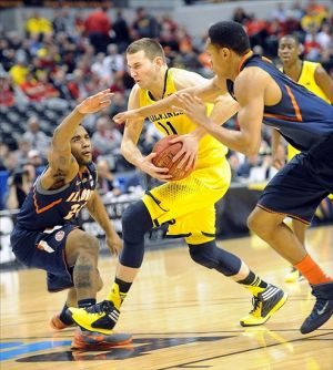 Mar 14, 2014; Indianapolis, IN, USA; Michigan Wolverines guard Nik Stauskas (11) drives between Illinois Fighting Illini guard Rayvonte Rice (24) and guard Joeseph Bertrand (2) in the first half in the quarterfinals of the Big Ten college basketball tournament at Bankers Life Fieldhouse. Mandatory Credit: Thomas J. Russo-USA TODAY Sports