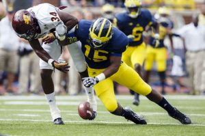 Aug 31, 2013; Ann Arbor, MI, USA; Central Michigan Chippewas running back Zurlon Tipton (34) and Michigan Wolverines linebacker James Ross III (15) reach for the ball in the first quarter at Michigan Stadium. Mandatory Credit: Rick Osentoski-USA TODAY Sports