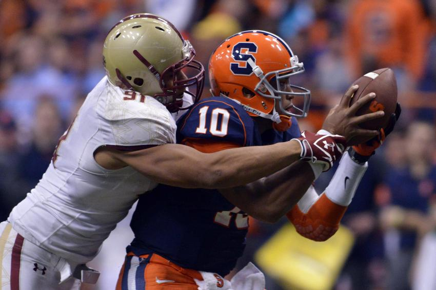 Nov 30, 2013; Syracuse, NY, USA; Boston College Eagles defensive end Kasim Edebali (91) wrestles Syracuse Orange quarterback Terrel Hunt (10) for the ball after he blocked a pass attempt during the fourth quarter of a game at the Carrier Dome. Syracuse won the game 34-31. Mandatory Credit: Mark Konezny-USA TODAY Sports