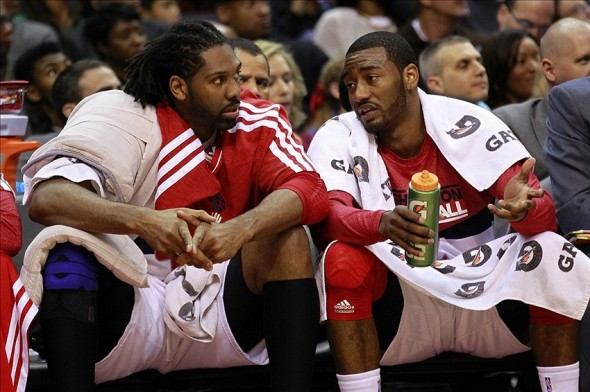 March 3, 2013; Washington, DC, USA; Washington Wizards point guard John Wall (right) talks with Wizards center Nene (left) on the bench against the Philadelphia 76ers in the second quarter at Verizon Center. The Wizards won 90-87. Mandatory Credit: Geoff Burke-USA TODAY Sports