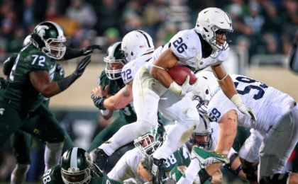 Nov 28, 2015; East Lansing, MI, USA; Penn State Nittany Lions running back Saquon Barkley (26) leaps over Michigan State Spartans defensive end Demetrius Cooper (98) during the second half of a game at Spartan Stadium. Mandatory Credit: Mike Carter-USA TODAY Sports