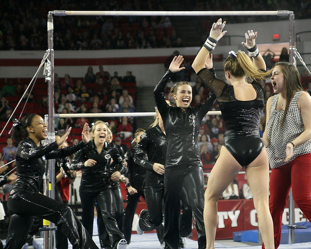 Mary Beth Box is the first to congratulate Brittany Rogers after her uneven bars routine.
