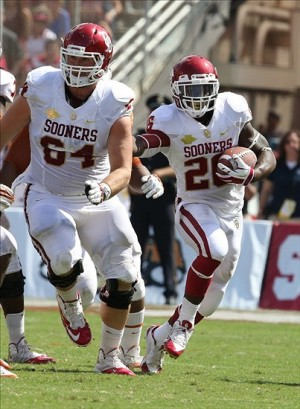 Oct 12, 2013; Dallas, TX, USA; Oklahoma Sooners running back Damien Williams (26) runs with the ball with a lead block from center Gabe Ikard (64) against the Texas Longhorns during the Red River Rivalry at the Cotton Bowl Stadium. Mandatory Credit: Matthew Emmons-USA TODAY Sports