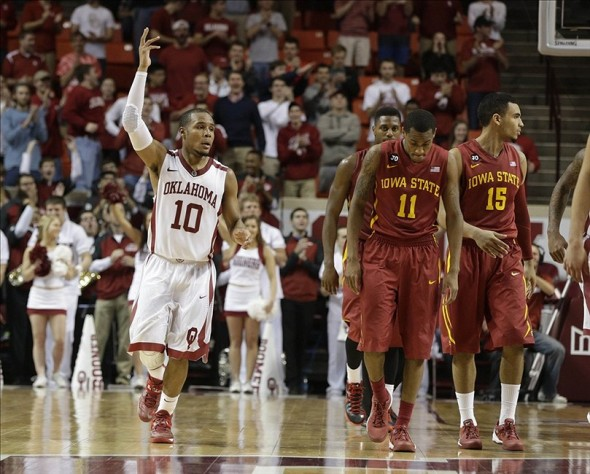 Jan 11, 2014; Norman, OK, USA; Oklahoma Sooners guard Jordan Woodard (10) reacts to a foul with Iowa State Cyclones guard Monte Morris (11) on the court in the scone half at Lloyd Noble Center. Oklahoma beat Iowa State 87-82. Mandatory Credit: Tim Heitman-USA TODAY Sports