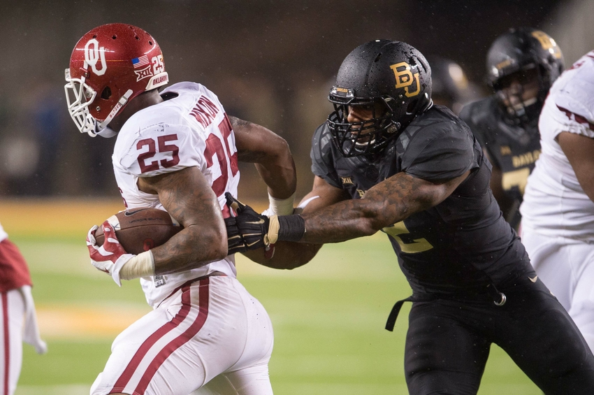 Nov 14, 2015; Waco, TX, USA; Oklahoma Sooners running back Joe Mixon (25) tries to elude Baylor Bears defensive end Shawn Oakman (2) during the game at McLane Stadium. The Sooners defeat the Bears 44-34. Mandatory Credit: Jerome Miron-USA TODAY Sports