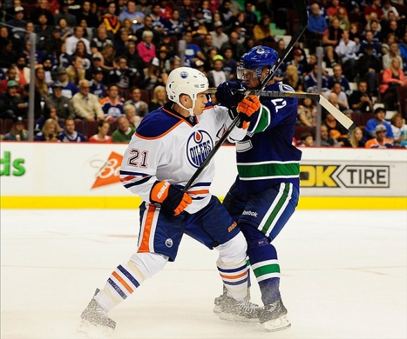 NHL: Preseason-Edmonton Oilers at Vancouver Canucks Sep 18, 2013; Vancouver, British Columbia, CAN; Edmonton Oilers defenseman Andrew Ference (21) and Vancouver Canucks forward Daniel Sedin (22) during the third period at Rogers Arena. The Edmonton Oilers won 4-1. Mandatory Credit: Anne-Marie Sorvin-USA TODAY Sports