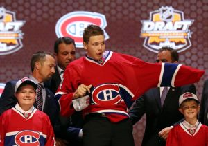 Jun 27, 2014; Philadelphia, PA, USA; Nikita Scherbak puts on a team sweater after being selected as the number twenty-six overall pick to the Montreal Canadiens in the first round of the 2014 NHL Draft at Wells Fargo Center. Mandatory Credit: Bill Streicher-USA TODAY Sports