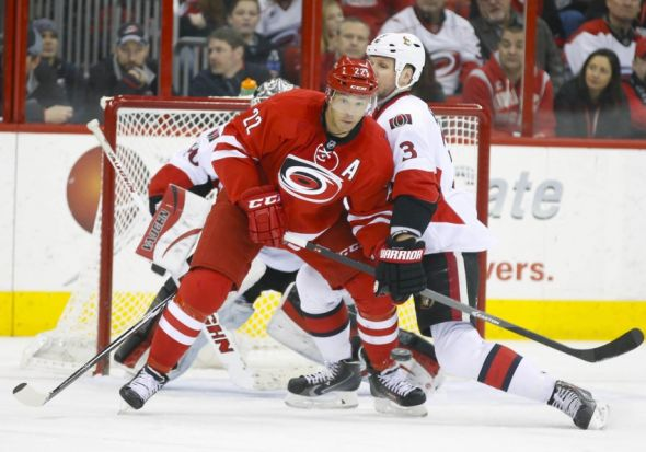 Jan 25, 2014; Raleigh, NC, USA; Ottawa Senators defensemen Marc Methot (3) battles for position with the Carolina Hurricanes forward Manny Malhotra (22) during the 2nd period at PNC Arena. Mandatory Credit: James Guillory-USA TODAY Sports