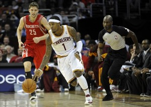 Feb 28, 2012; Cleveland, OH, USA; Cleveland Cavaliers shooting guard Daniel Gibson (1) dribbles up the court after picking up a loose ball against Houston Rockets forward Chandler Parsons (25) as referee Sir Allen Conner follows the action in the fourth quarter at Quicken Loans Arena. Mandatory Credit: David Richard-US PRESSWIRE