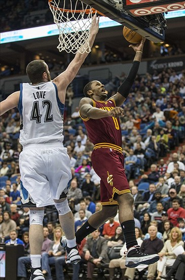 Dec 7, 2012; Minneapolis, MN, USA; Cleveland Cavaliers small forward C.J. Miles (0) goes up for a layup past Minnesota Timberwolves power forward Kevin Love (42) in the second half at Target Center. The Minnesota Timberwolves won 91-73. Mandatory Credit: Jesse Johnson-USA TODAY Sports