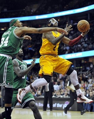 Jan 22, 2013; Cleveland, OH, USA; Cleveland Cavaliers point guard Kyrie Irving (2) makes a layup while being fouled by Boston Celtics small forward Paul Pierce (34) in the fourth quarter at Quicken Loans Arena. Mandatory Credit: David Richard-USA TODAY Sports