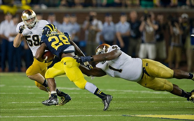 Sep 7, 2013; Ann Arbor, MI, USA; Michigan Wolverines running back Fitzgerald Toussaint (28) carries the ball as Notre Dame Fighting Irish nose tackle Louis Nix (1) and linebacker Jarrett Grace (59) defend in the third quarter at Michigan Stadium. Michigan won 41-30. Mandatory Credit: Matt Cashore-USA TODAY Sports