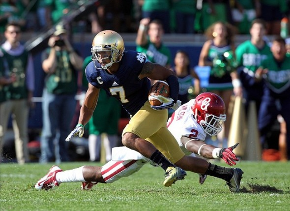 Sep 28, 2013; South Bend, IN, USA; Notre Dame Fighting Irish wide receiver T.J. Jones (7) runs past Oklahoma Sooners defensive back Julian Wilson (2) at Notre Dame Stadium. Mandatory Credit: Brian Spurlock-USA TODAY Sports