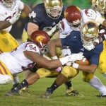 Oct 19, 2013; South Bend, IN, USA; Southern California Trojans defensive end Leonard Williams (94) and linebacker Lamar Dawson (55) tackle Notre Dame Fighting Irish running back George Atkinson III (4) at Notre Dame Stadium. Notre Dame defeated USC 14-10. Mandatory Credit: Kirby Lee-USA TODAY Sports