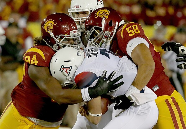 USC defensive linemen Leonard Williams (94) and J.R. Tavai (58) sack Arizona quarterback B.J. Denker at the Coliseum in Los Angeles. (Luis Sinco / Los Angeles Times / October 10, 2013)