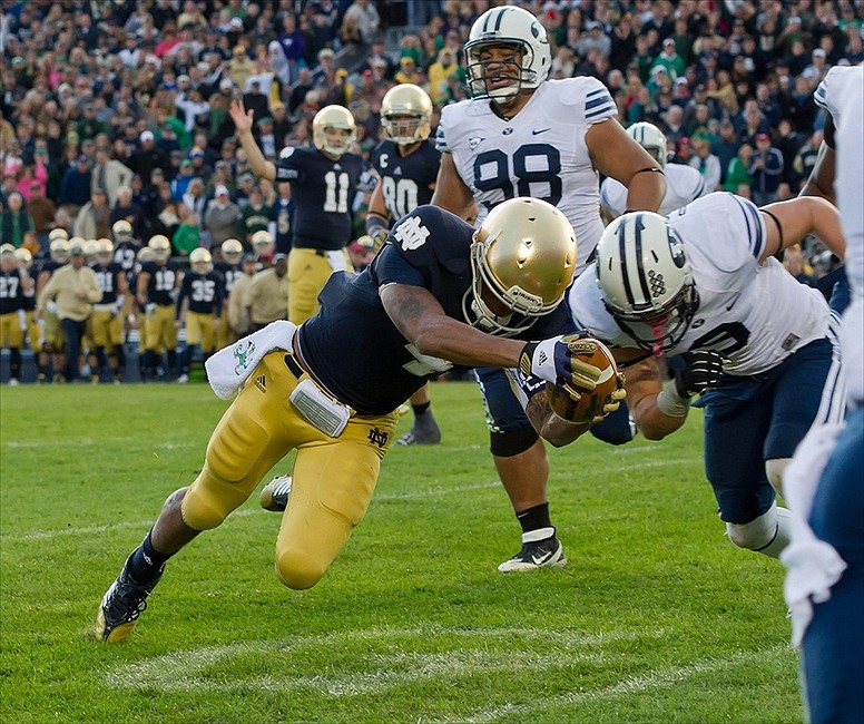 Oct. 20, 2012; South Bend, IN, USA; Notre Dame Fighting Irish running back George Atkinson III (4) stretches the ball across the goal line for a touchdown as BYU Cougars defensive back Daniel Sorensen (9) defends in the fourth quarter at Notre Dame Stadium. Notre Dame won 17-14. Mandatory Credit: Matt Cashore-USA TODAY Sports