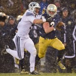 Nov 23, 2013; South Bend, IN, USA; Notre Dame Fighting Irish running back Cam McDaniel (33) carries the ball as BYU Cougars linebacker Alani Fua (5) defends in the second quarter at Notre Dame Stadium. Mandatory Credit: Matt Cashore-USA TODAY Sports