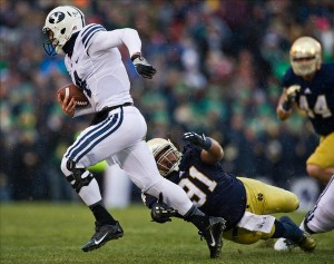 Nov 23, 2013; South Bend, IN, USA; BYU Cougars quarterback Taysom Hill (4) carries the ball as Notre Dame Fighting Irish defensive end Sheldon Day (91) attempts to tackle in the first quarter at Notre Dame Stadium. Mandatory Credit: Matt Cashore-USA TODAY Sports