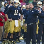 Dec 28, 2013; Bronx, NY, USA; Notre Dame Fighting Irish head coach Brian Kelly talks with quarterback Tommy Rees (11) in the first quarter of the Pinstripe Bowl against the Rutgers Scarlet Knights at Yankee Stadium. Mandatory Credit: Matt Cashore-USA TODAY Sports