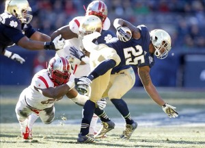 Dec 28, 2013; Bronx, NY, USA; Rutgers Scarlet Knights linebacker Quentin Gause (50) tackles Notre Dame Fighting Irish running back Tarean Folston (25) during the first half in the Pinstripe Bowl at Yankee Stadium. Mandatory Credit: Andrew Mills/THE STAR-LEDGER via USA TODAY Sports