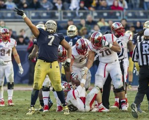 Dec 28, 2013; Bronx, NY, USA; Notre Dame Fighting Irish defensive end Stephon Tuitt (7) celebrates after sacking Rutgers Scarlet Knights quarterback Chas Dodd (19) in the fourth quarter of the Pinstripe Bowl at Yankee Stadium. Notre Dame won 29-16. Mandatory Credit: Matt Cashore-USA TODAY Sports