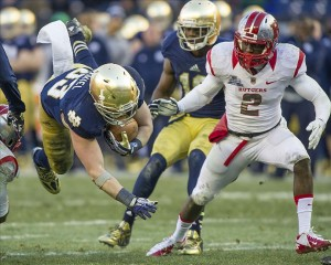 Dec 28, 2013; Bronx, NY, USA; Notre Dame Fighting Irish running back Cam McDaniel (33) dives for extra yards in front of Rutgers Scarlet Knights cornerback Gareef Glashen (2) in the third quarter of the Pinstripe Bowl at Yankee Stadium. Notre Dame won 29-16. Mandatory Credit: Matt Cashore-USA TODAY Sports