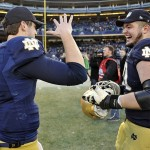 Dec 28, 2013; Bronx, NY, USA; Notre Dame Fighting Irish offensive tackle Zack Martin (70) and Notre Dame Fighting Irish quarterback Tommy Rees (11) celebrate against the Rutgers Scarlet Knights after the Pinstripe Bowl at Yankees Stadium. Notre Dame Fighting Irish won the game 29-16. Mandatory Credit: Joe Camporeale-USA TODAY Sports