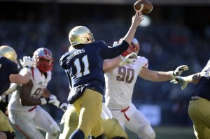 Dec 28, 2013; Bronx, NY, USA; Notre Dame Fighting Irish quarterback Tommy Rees (11) throws a pass against the Rutgers Scarlet Knights during the first half of the Pinstripe Bowl at Yankees Stadium. Notre Dame Fighting Irish won the game 29-16. Mandatory Credit: Joe Camporeale-USA TODAY Sports