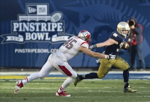 Dec 28, 2013; Bronx, NY, USA; Notre Dame Fighting Irish running back Cam McDaniel (33) runs the ball as Rutgers Scarlet Knights linebacker Kevin Snyder (45) defends in the third quarter of the Pinstripe Bowl at Yankee Stadium. Notre Dame won 29-16. Mandatory Credit: Matt Cashore-USA TODAY Sports