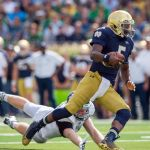 Aug 30, 2014; South Bend, IN, USA; Notre Dame Fighting Irish quarterback Everett Golson (5) runs for a touchdown as Rice Owls defensive end Brian Nordstrom (47) attempts to tackle in the second quarter at Notre Dame Stadium. Mandatory Credit: Matt Cashore-USA TODAY Sports