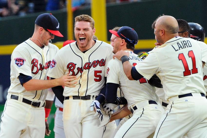 Apr 27, 2014; Atlanta, GA, USA; Atlanta Braves first baseman Freddie Freeman (5) reacts with team mates after driving in the game winning run with a hit against the Cincinnati Reds during the tenth inning at Turner Field. The Braves defeated the Reds 1-0 in ten innings. Mandatory Credit: Dale Zanine-USA TODAY Sports