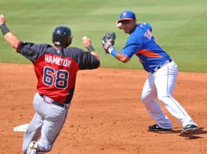 Mar 9, 2014; Port St. Lucie, FL, USA; New York Mets shortstop Ruben Tejada (11) turns the double play over Atlanta Braves first baseman Mark Hamilton (68) in spring training action at Tradition Stadium. Mandatory Credit: Brad Barr-USA TODAY Sports