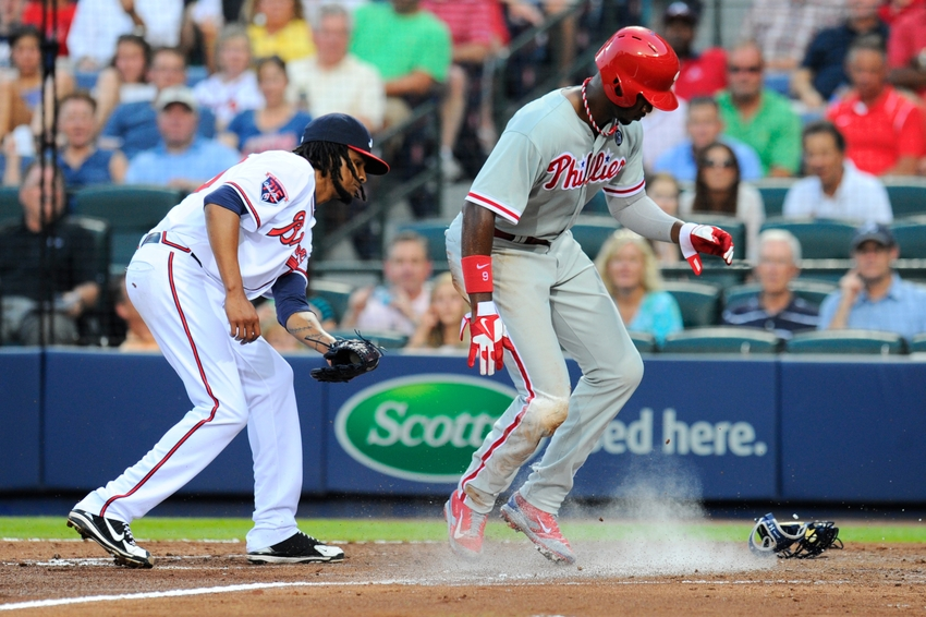 Jun 17, 2014; Atlanta, GA, USA; Philadelphia Phillies left fielder Domonic Brown (9) scores in front of Atlanta Braves starting pitcher Ervin Santana (30) after a passed ball during the fourth inning at Turner Field. Mandatory Credit: Dale Zanine-USA TODAY Sports