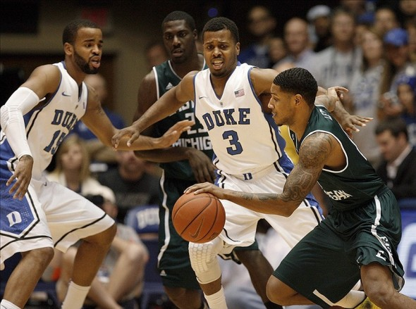 Dec 28, 2013; Durham, NC, USA; Eastern Michigan Eagles guard Raven Lee (0) drives against Duke Blue Devils guard Tyler Thornton (3) and forward Josh Hairston (15) during the game at Cameron Indoor Stadium. Mandatory Credit: Mark Dolejs-USA TODAY Sports