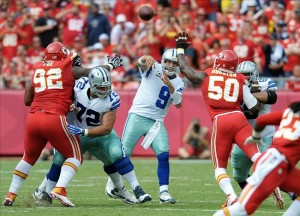 Sep 15, 2013; Kansas City, MO, USA; Dallas Cowboys quarterback Tony Romo (9) throws a pass as Kansas City Chiefs outside linebacker Justin Houston (50) during the first half at Arrowhead Stadium. Mandatory Credit: Denny Medley-USA TODAY Sports