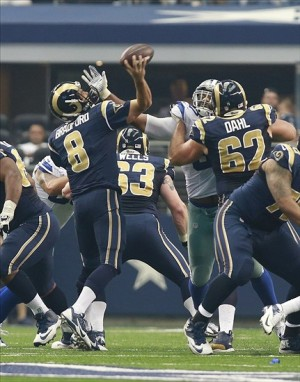 Sep 22, 2013; Arlington, TX, USA; St. Louis Rams quarterback Sam Bradford (8) is hit by Dallas Cowboys defensive end Anthony Spencer (93) during the game at AT
