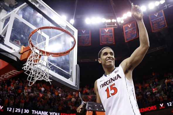 Mar 1, 2014; Charlottesville, VA, USA; Virginia Cavaliers guard Malcolm Brogdon (15) celebrates with the net after the Cavaliers game against the Syracuse Orange at John Paul Jones Arena. The Cavaliers won 75-56 and clinched the ACC regular season title. Mandatory Credit: Geoff Burke-USA TODAY Sports