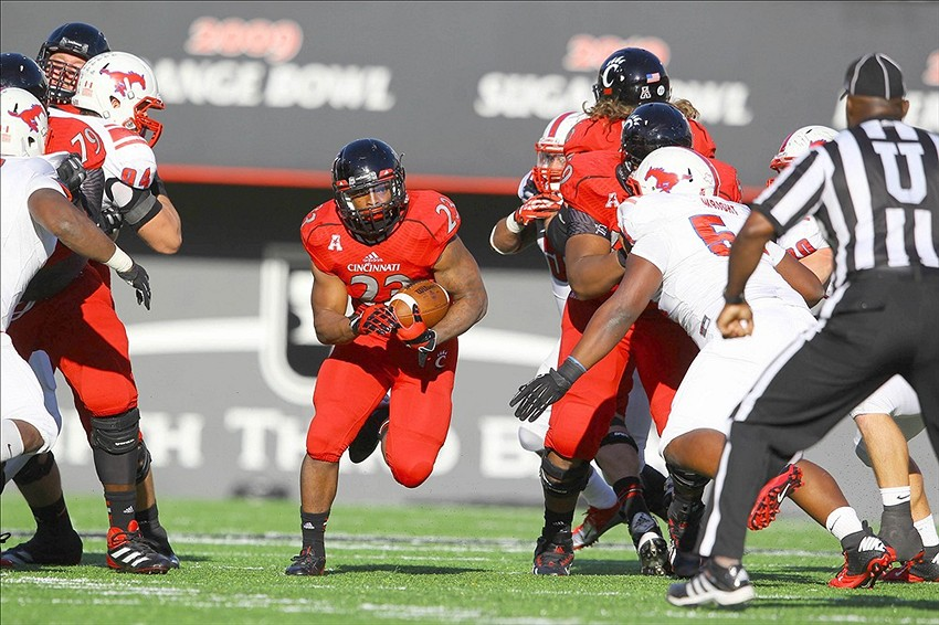 Nov 9, 2013; Cincinnati, OH, USA; Cincinnati Bearcats running back Hosey Williams (23) runs through a hole during the closing minutes of the Bearcats 28-25 win over the Southern Methodist Mustangs at Nippert Stadium. Mandatory Credit: Rob Leifheit-USA TODAY Sports