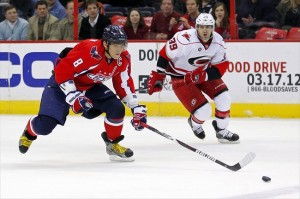 March 6, 2012; Washington, DC, USA; Washington Capitals left wing Alex Ovechkin (8) skates with the puck as Carolina Hurricanes right wing Patrick Dwyer (39) chases in the first period at Verizon Center. The Hurricanes won 4-3 in overtime. Mandatory Credit: Geoff Burke-USA TODAY Sports