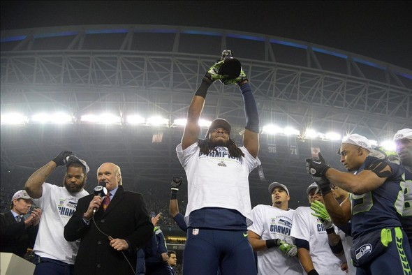 Jan 19, 2014; Seattle, WA, USA; Seattle Seahawks cornerback Richard Sherman hoists the George Halas Trophy after the 2013 NFC Championship football game against the San Francisco 49ers at CenturyLink Field. Mandatory Credit: Kirby Lee-USA TODAY Sports