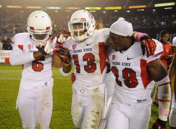 Oct 26, 2013; San Diego, CA, USA; Fresno State Bulldogs safety Derron Smith (13) celebrates with teammates after making a defensive stop in overtime to secure a 35-28 win against the San Diego State Aztecs at Qualcomm Stadium. Mandatory Credit: Christopher Hanewinckel-USA TODAY Sports