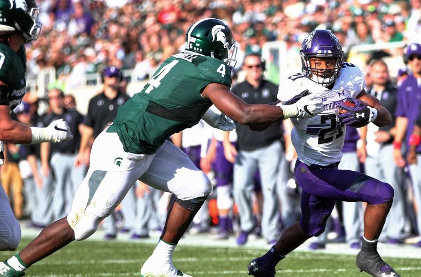 Oct 15, 2016; East Lansing, MI, USA; Northwestern Wildcats running back Justin Jackson (21) is chased down by Michigan State Spartans defensive lineman Malik McDowell (4) during the first half of a game at Spartan Stadium. Mandatory Credit: Mike Carter-USA TODAY Sports