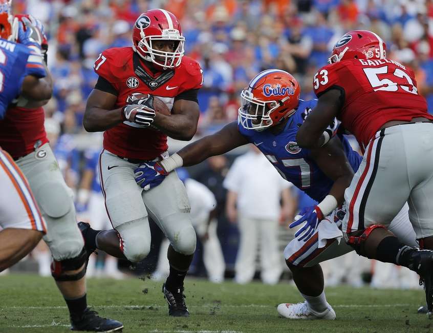Oct 29, 2016; Jacksonville, FL, USA; Georgia Bulldogs running back Nick Chubb (27) runs with the ball as Florida Gators defensive lineman Caleb Brantley (57) defends during the first half at EverBank Field. Mandatory Credit: Kim Klement-USA TODAY Sports