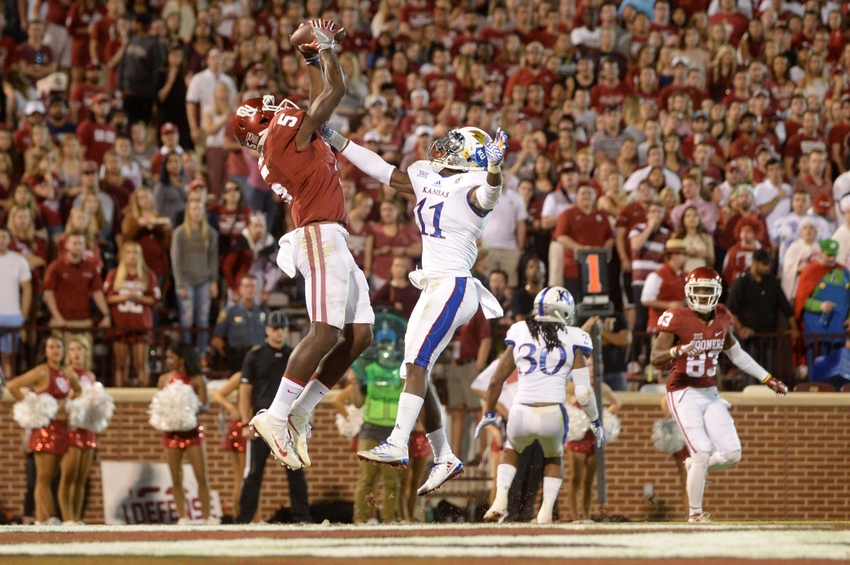 Oct 29, 2016; Norman, OK, USA; Oklahoma Sooners wide receiver Geno Lewis (5) catches a touchdown pass in the endzone while being defended by Kansas Jayhawks linebacker Mike Lee (11) during the third quarter at Gaylord Family - Oklahoma Memorial Stadium. Mandatory Credit: Mark D. Smith-USA TODAY Sports