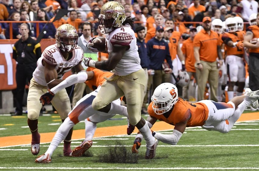 Nov 19, 2016; Syracuse, NY, USA; Florida State Seminoles running back Dalvin Cook (4) scores a rushing touchdown as Syracuse Orange defensive back Daivon Ellison (19) dives in an attempt to make a tackle during the third quarter of a game at the Carrier Dome. Florida State won 45-14. Mandatory Credit: Mark Konezny-USA TODAY Sports
