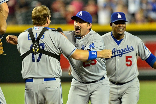 Sep 19, 2013; Phoenix, AZ, USA; Los Angeles Dodgers catcher A.J. Ellis (17) celebrates with left fielder Scott Van Slyke (33) and third baseman Juan Uribe (5) after beating the Arizona Diamondbacks 7-6 at Chase Field. Mandatory Credit: Matt Kartozian-USA TODAY Sports