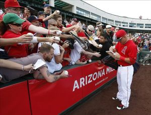 Mar 2, 2014; Tempe, AZ, USA; Los Angeles Angels center fielder Mike Trout (27) signs autographs before a game against the Oakland Athletics at Tempe Diablo Stadium. Mandatory Credit: Rick Scuteri-USA TODAY Sports